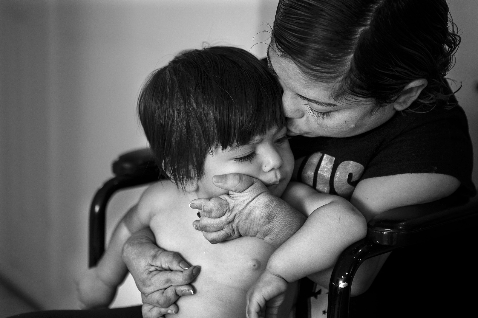 Rosa Caceres kisses her daughter Daniela Figueroa, 11 months, at their home in Lake Worth on Wednesday, November 18, 2015. Rosa has debilitating rheumatoid arthritis which forces her to use a wheelchair. Sometimes the pain in her joints is so bad that Rosa cannot even feed herself let alone hold her daughters.