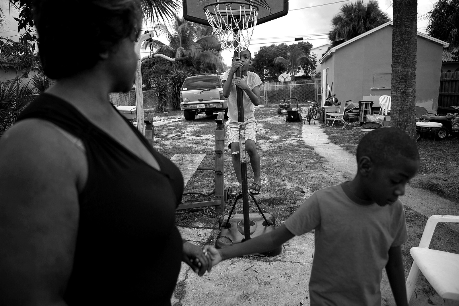 Omari Tripp, 8, climbs up the basketball hoop in his backyard as his brother Odarius, 6, pulls their mother Angeline back inside. Both Omari and Odarius have severe autism and require nearly constant supervision.