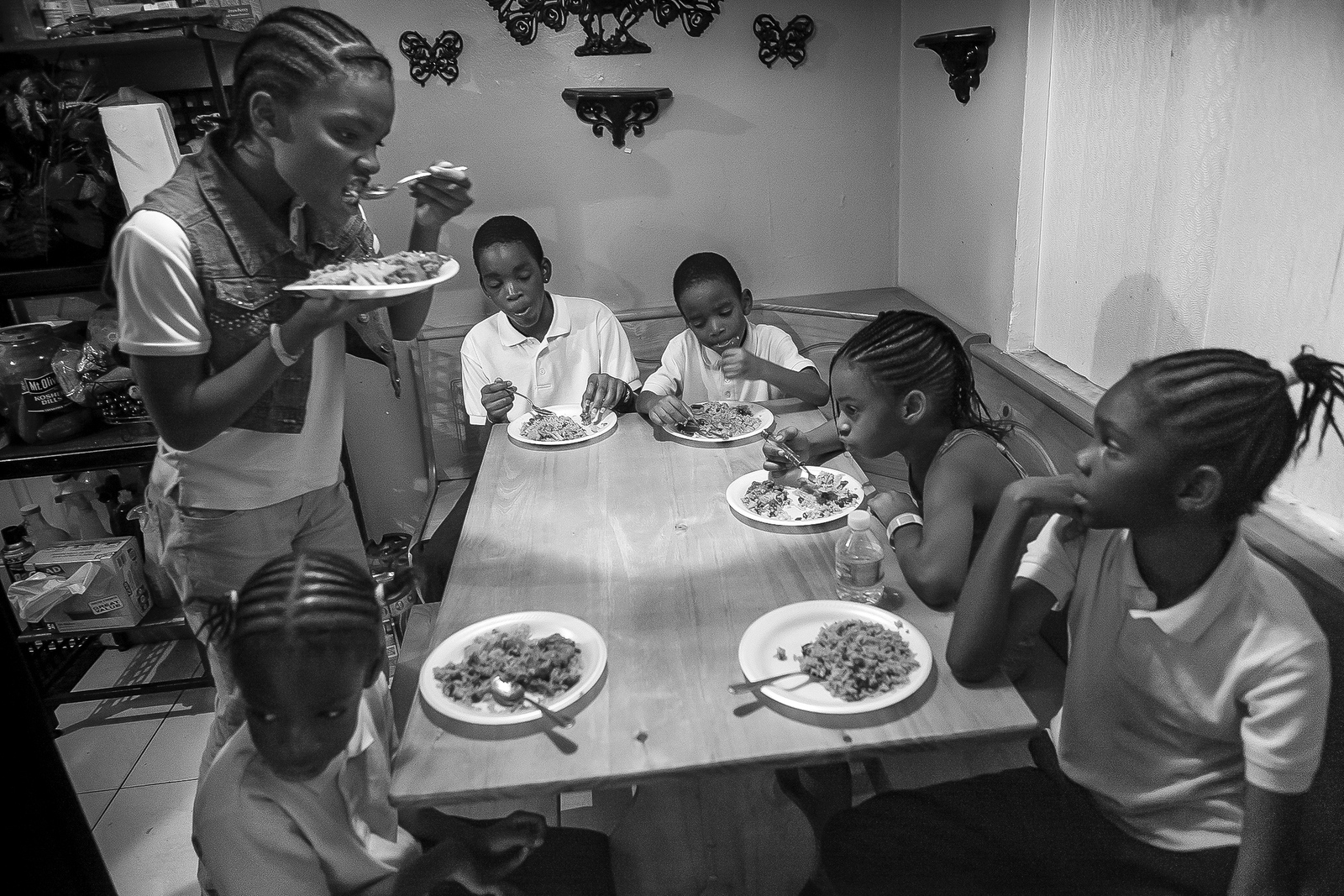 Part of the Fitzgerald family, left to right,Jernyah, Jermiah, Jermaine, Keyshawn, their cousin Joanna Fitzgerald and Jerqueriria squeeze around their grandmother Joann's kitchen table for dinner. Joann adopted six of her grandchildren and is working to gain custody of their older sister as she builds a new life focused around providing the children with a safe, stable environment.