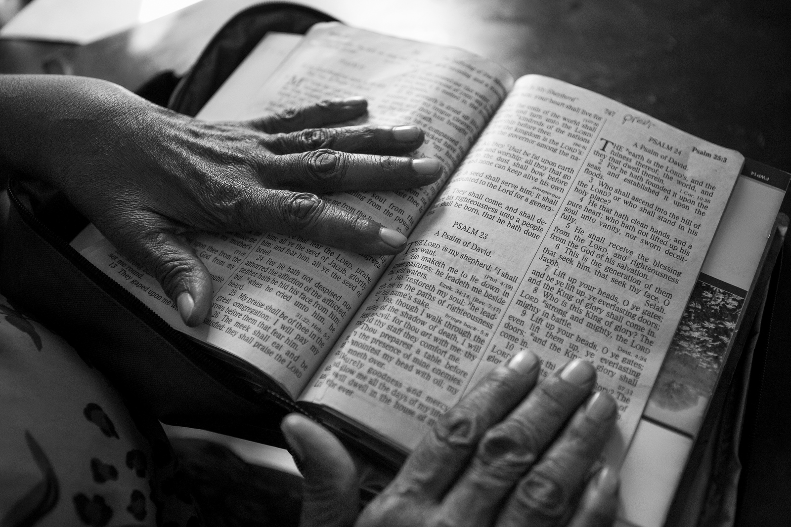 Imogene Davis opens the Bible to her favorite Psalm at her house in Belle Glade. Imogene's previous home caught fire and the family lost everything. Imogene says that her faith helps to keep her going, but sometimes she gets overwhelmed and can't stop crying.