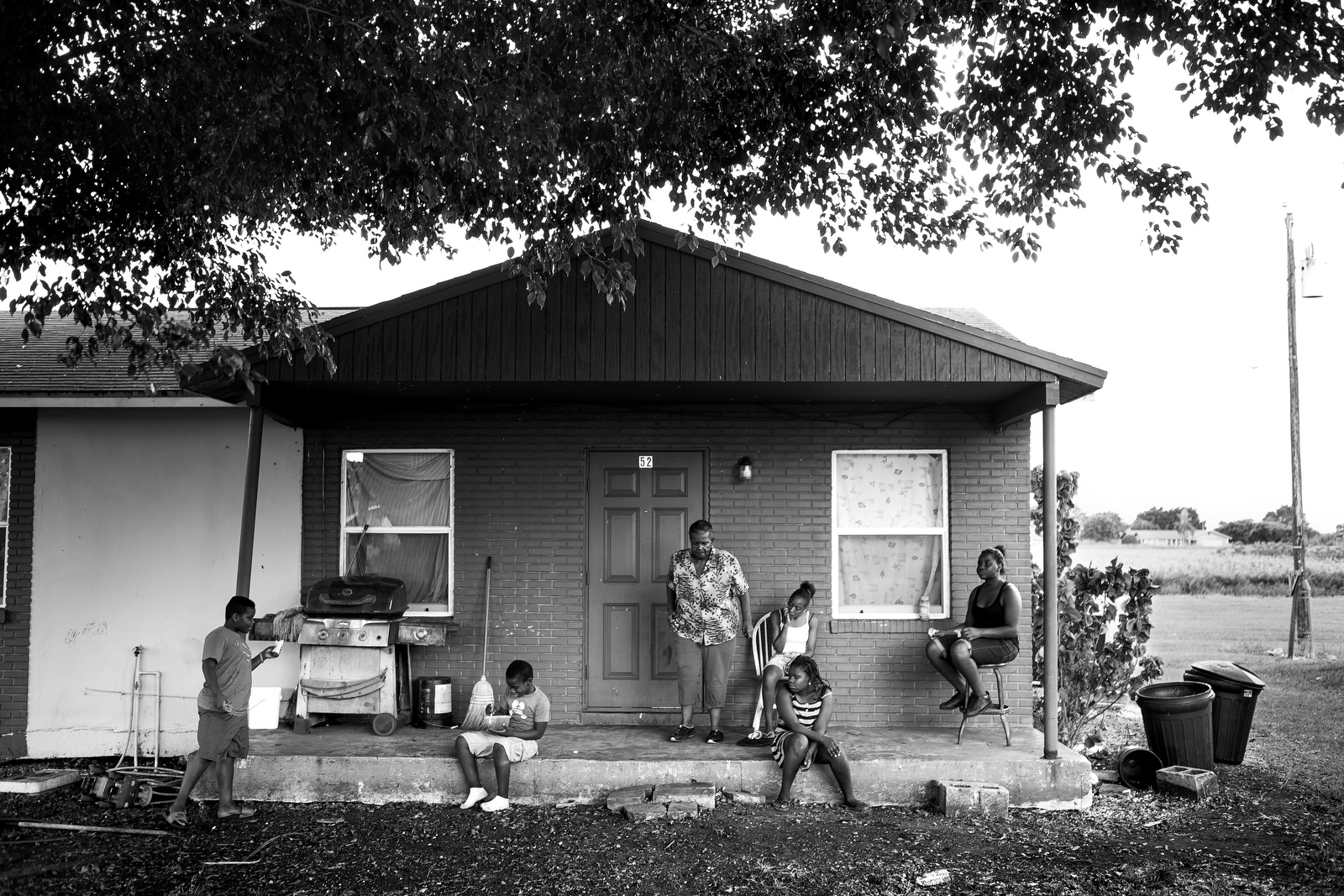 Imogene Davis leaves her house as her grandchildren and their friends sit on the porch. Imogene was a farmworker for the same company for 42 years. Her husband Jimmy Lee Davis still works on a farm but at the age of 64, he will not be able to provide that income for the family much longer.