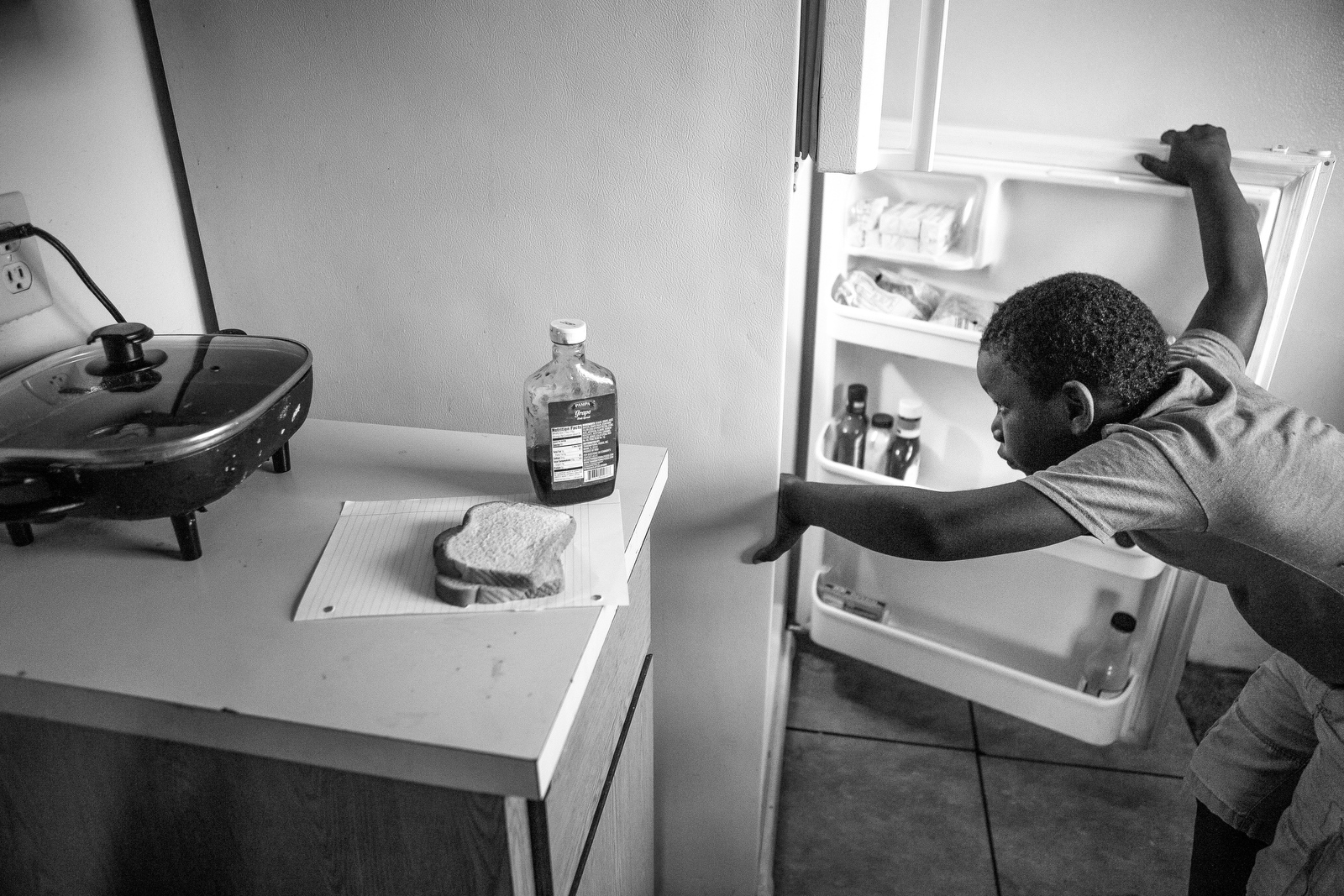 Donald Gibson, 8, checks the refrigerator before making a peanut butter and jelly sandwich at the home where he lives with his grandparents. Their previous home burned down and now Donald's grandmother Imogene only has one electric skillet to cook meal for the family of six. The family subsists primarily on her husband's sole farmworker's salary which means food can sometimes be scarce.