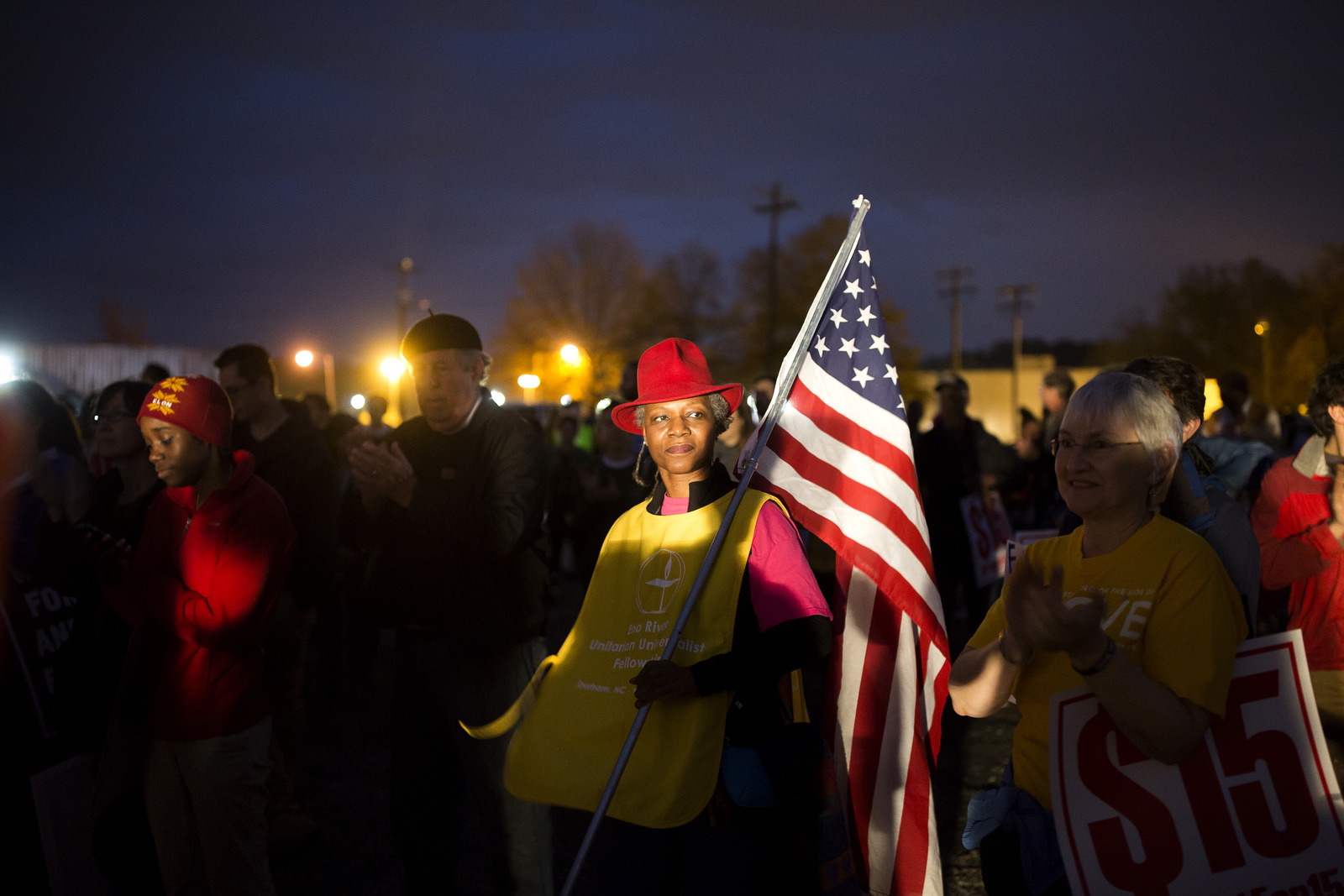 Joan Tilghman holds an American flag during a Fight for 15 minimum wage rally in Durham.