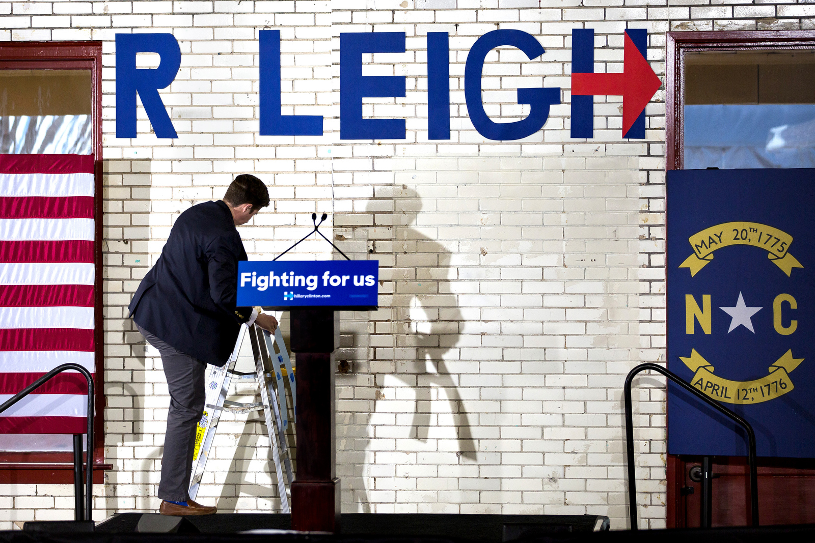 Paxton Howard, 25, of Raleigh, fixes a sign before Former President Bill Clinton speaks at a Get Out the Vote event to promote early voting for Hillary Clinton in Raleigh.