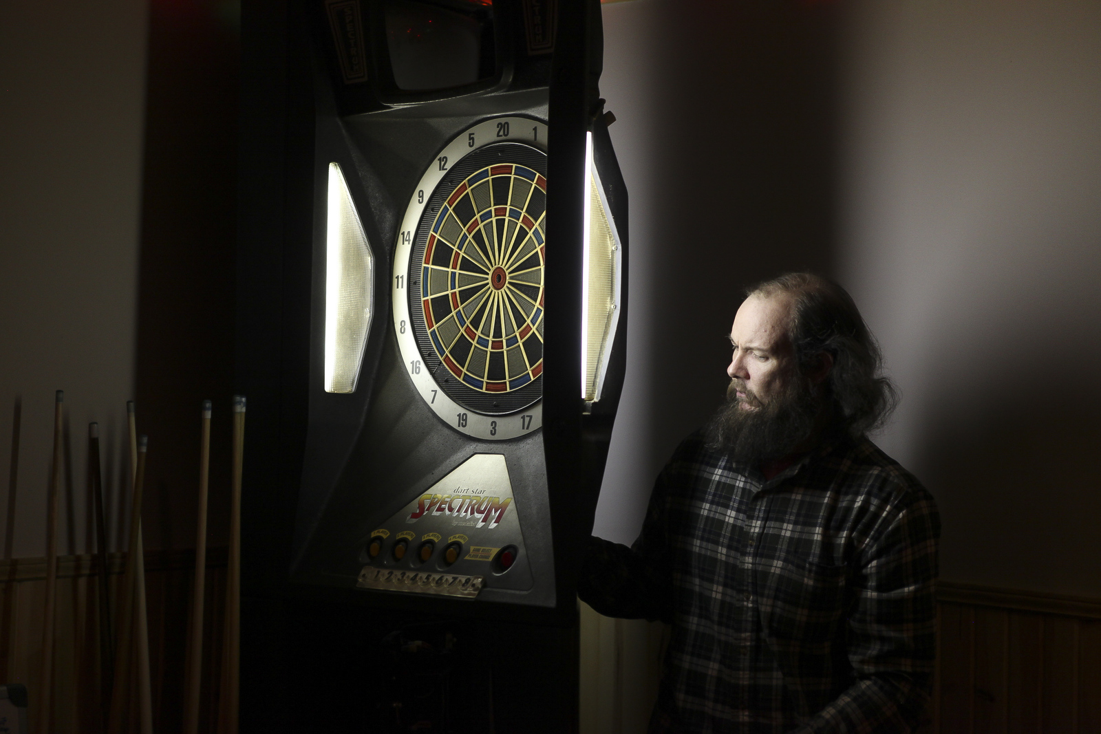 Jerramy Forrest fixes a dartboard at the Murray City American Legion. He travels throughout southeastern Ohio to replace electronic games. While Forrest was at the Legion, he also took a look at the jukebox to make sure it was working properly.
