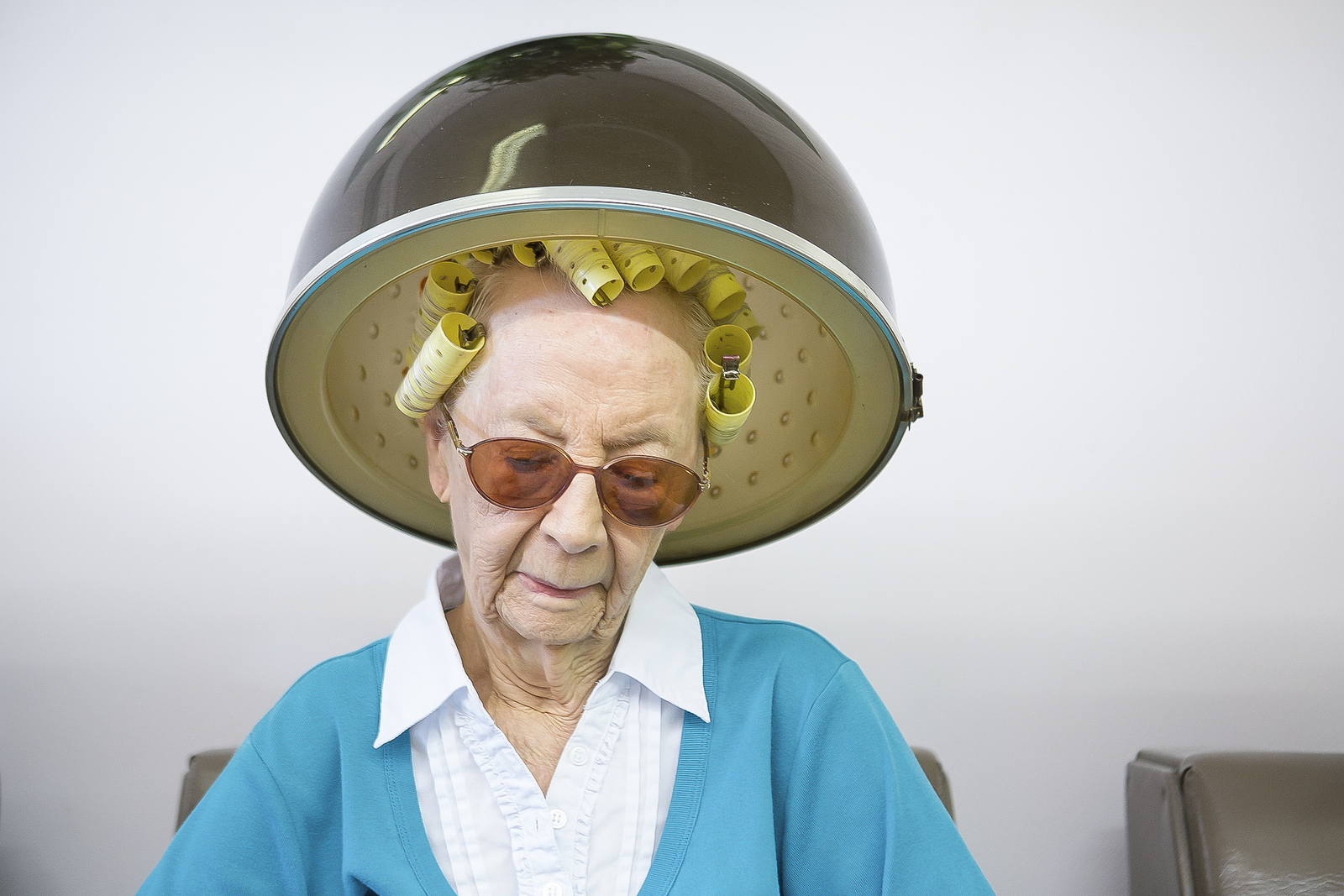 Mildred Kohler, 98, waits for her hair to dry at Fashionaire Salon. Tucked among the swirling traffic of a crowded strip mall, the salon is place that time appears to have passed by. Finding a customer under the age of 50 is hard to do as women in their 80s and 90s shuffle around to pick at sweet treats that owner Elaine Hill bakes everyday.