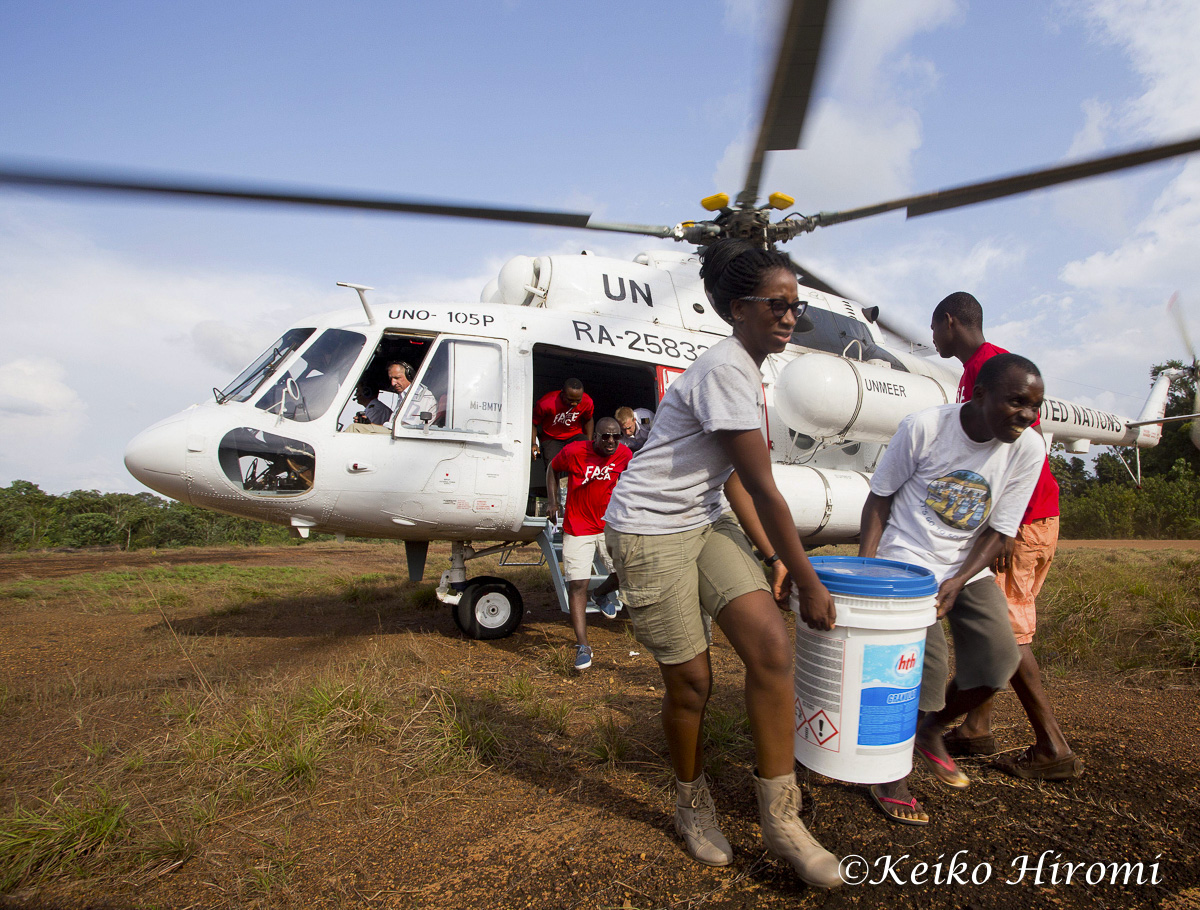 February 15 2015, Rivercess, Liberia: FACE Africa CEO Saran Kaba Jones carries a Safe Schools Initiative health and hygiene supply as UN helicopter delivers them to its implementation partner, FACE Africa in Neezuin Town, Rivercess, Liberia. The Safe School Initiative being rolled out this month, is funded by USAID (United States Agency for International Development), and coordinated by UNICEF in partnership with the Liberian Ministry of Education and other international and local partners to distribute hygiene kits and implementation of the hygiene kits at every school. The Safe Schools Initiative distributes hygiene kit to 4038 schools in Liberia. Based in U.S. and Monrovial, Liberia,FACE Africa is a implementation partner for Central Rivecess district 1 to distribution Hygiene kit to 26 schools in central Rivercess district 1. . Hygiene Kit includes chlorine, a table spoon (for chlorine measurement), a hands wash bucket with faucet, a bucket, robber gloves, rain boots, cleaning spray tank, stick brooms, hard brush, flip books, cloth, poster for hands wash, 2 thermal guns, manual books and check list for school principal. Liberian Schools have been closed due to the Ebola crisis since July, 2014. Schools are scheduled to open on March 2 in Rivercess.