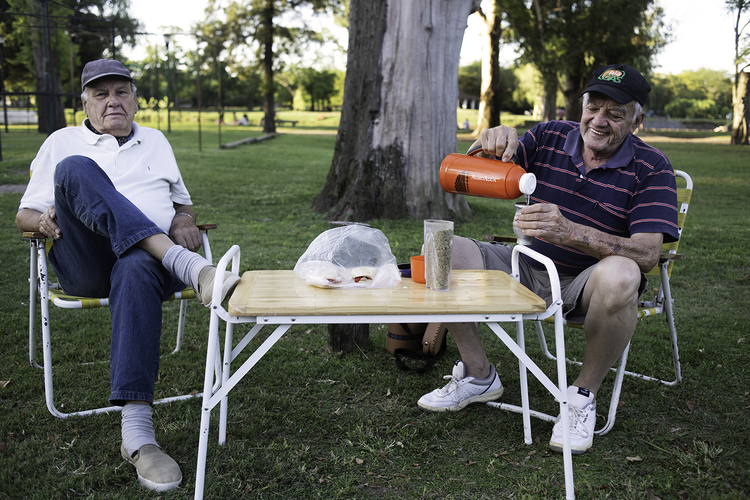 Two men drinking mate in a park. San Antonio de Areco, Argentina.