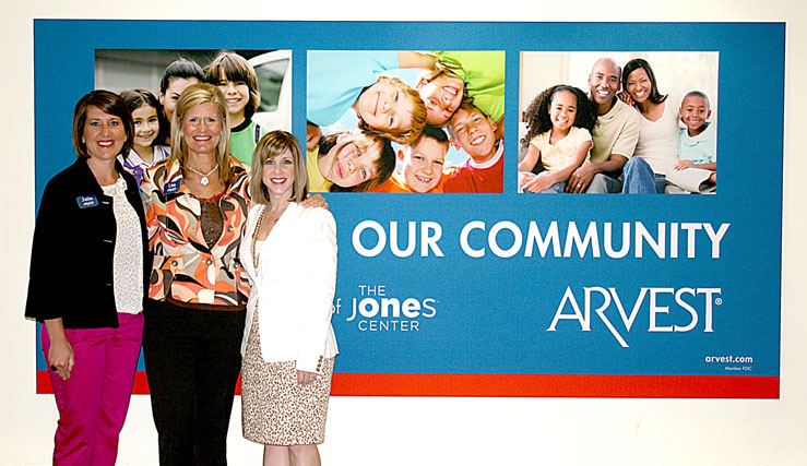 Unveiling of Arvest banner at The Jones Center   Lisa Ray, President/CEO, and Branch Administrator, Julie Shook, both of Arvest Springdale together with Kelly Kemp-McLintock, Chief Advancement Officer of The Jones Center, proudly displayed their new banner located in the Northern alcove. Arvest's corporate support provides important operating support for The Jones Center and its programs.