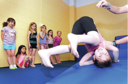 STAFF PHOTO SAMANTHA BAKER • @NWASAMANTHA Students watch as Emily Pozos, 5, practices a backwards roll during a beginning gymnastics class Wednesday at The Jones Center in Springdale.