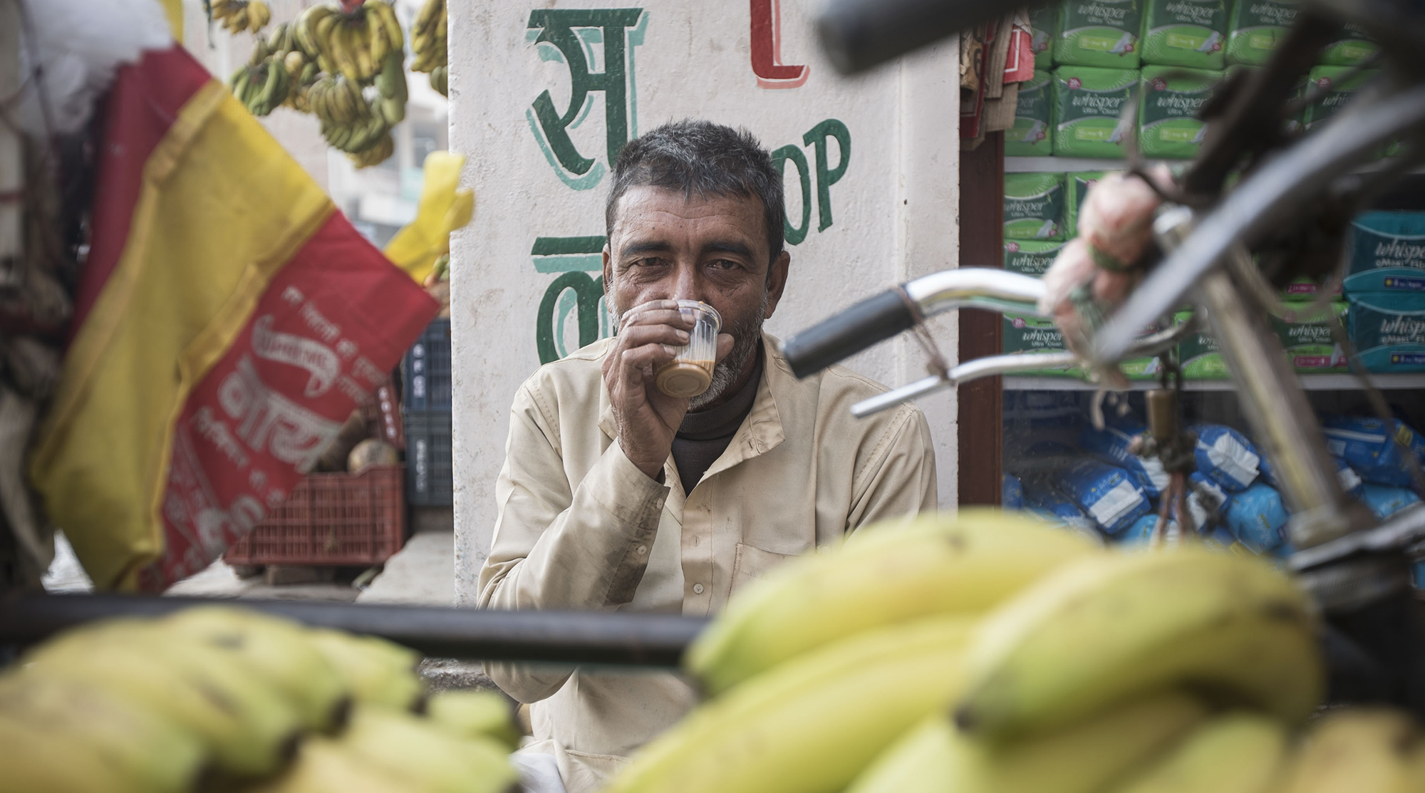 A local fruit vendor in Kathmandu having a cup of masala chai in the morning.