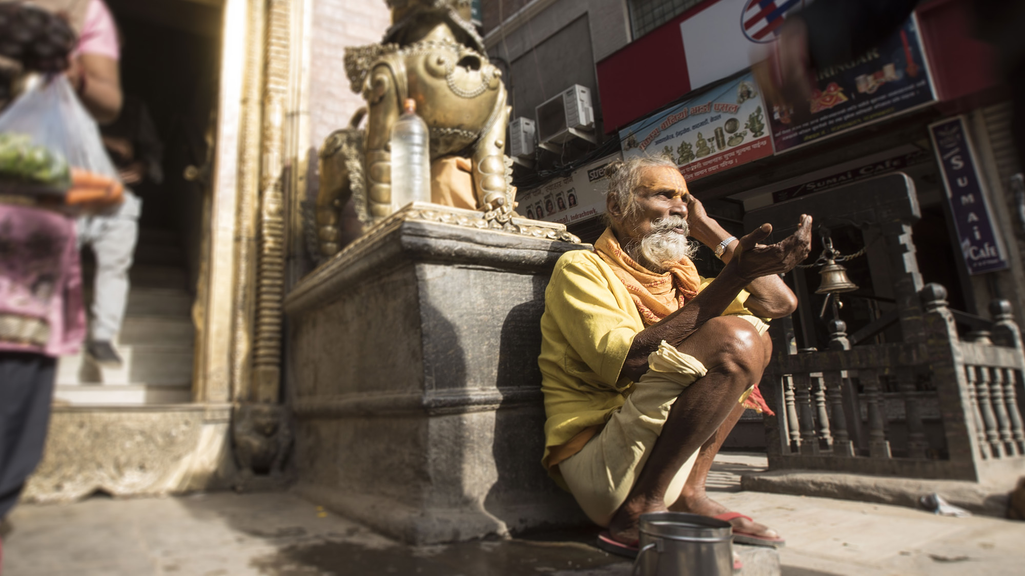 A holy man waits outside a temple for spare change.