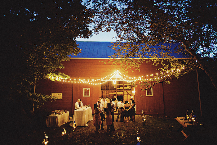 guests standing outside of red barn lit with string lights