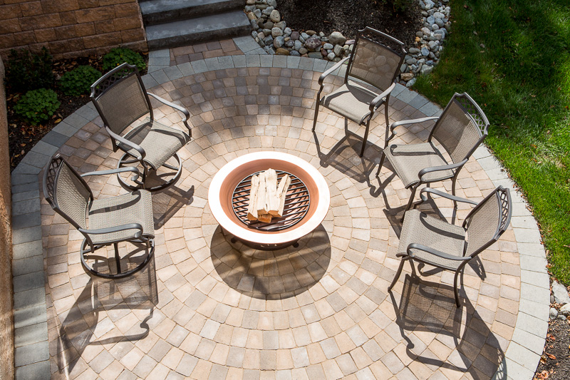 A firepit sits poised for sundown, ready to draw guests into casual conversation.