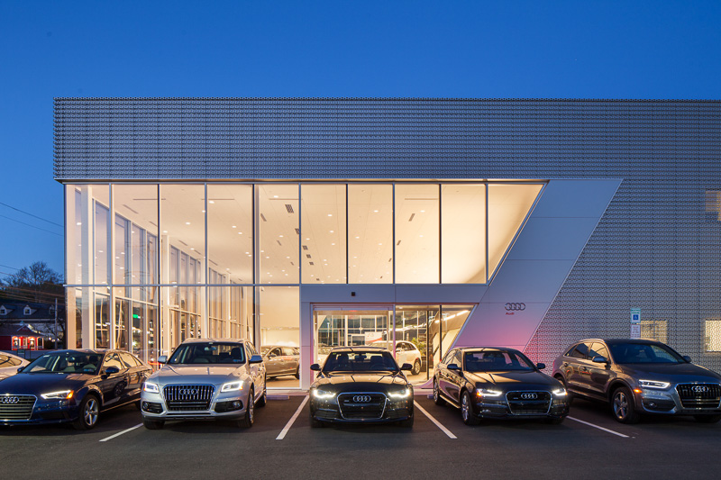 The sophisticated design of the showroom matches the luxury automobiles on display.