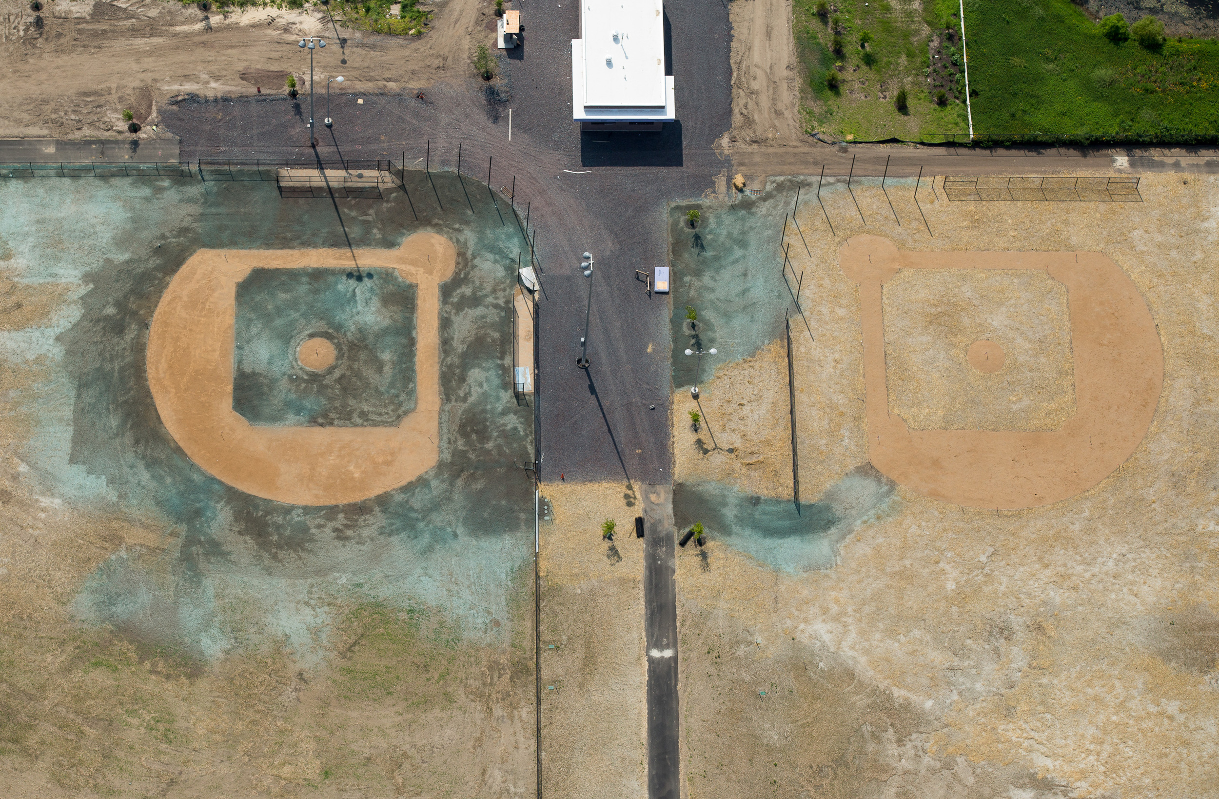 Two fields in Camden, NJ under construction, with new grass seed recently sprayed on the left.