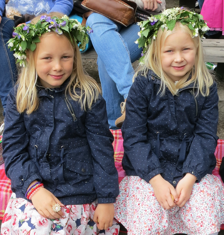 Young Swedish girls with garlands in their hair at a daytime Midsommer celebration.