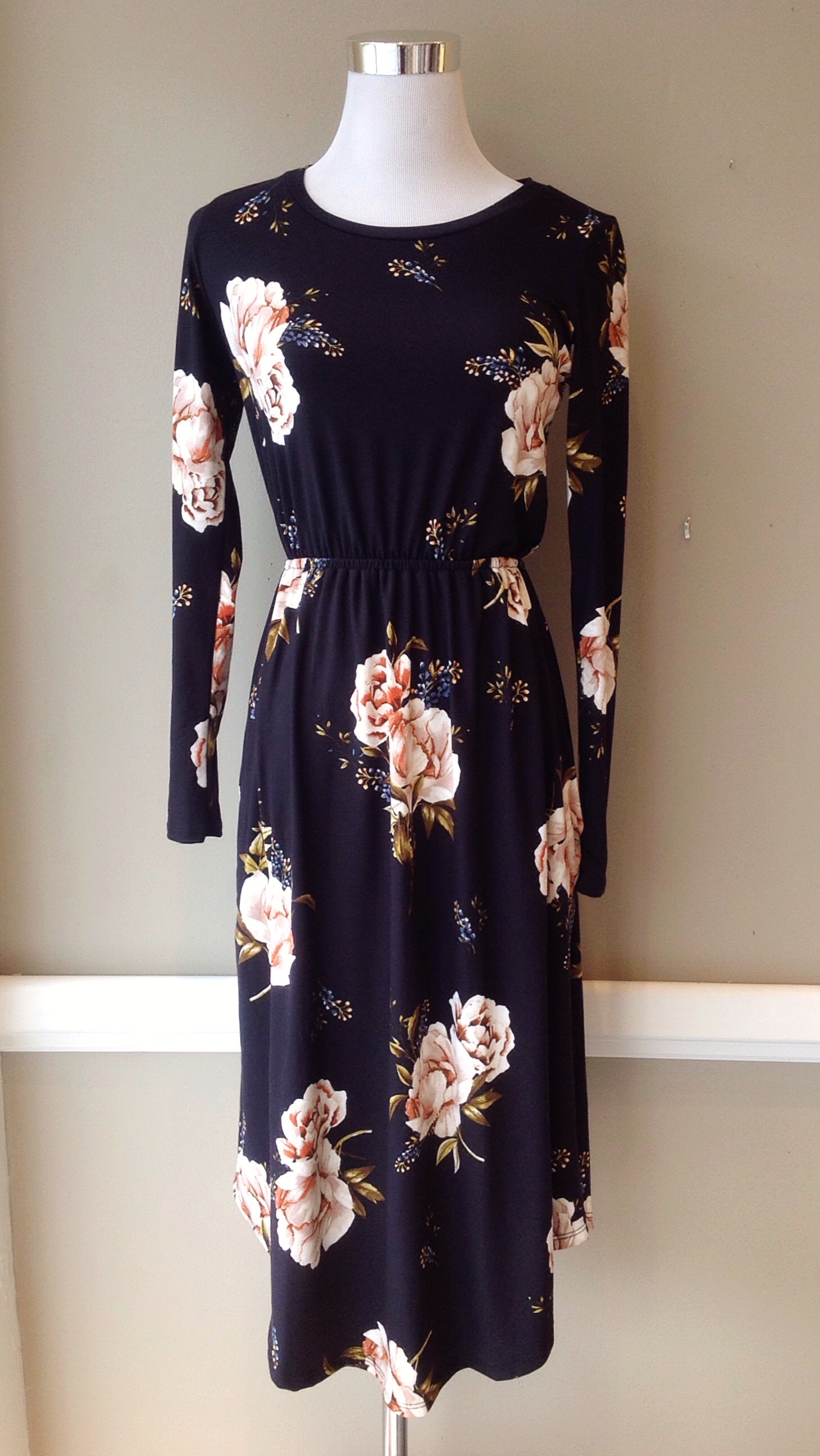 Long sleeve, soft knit dress with rounded hem and side seam pockets in black/pink floral, $38