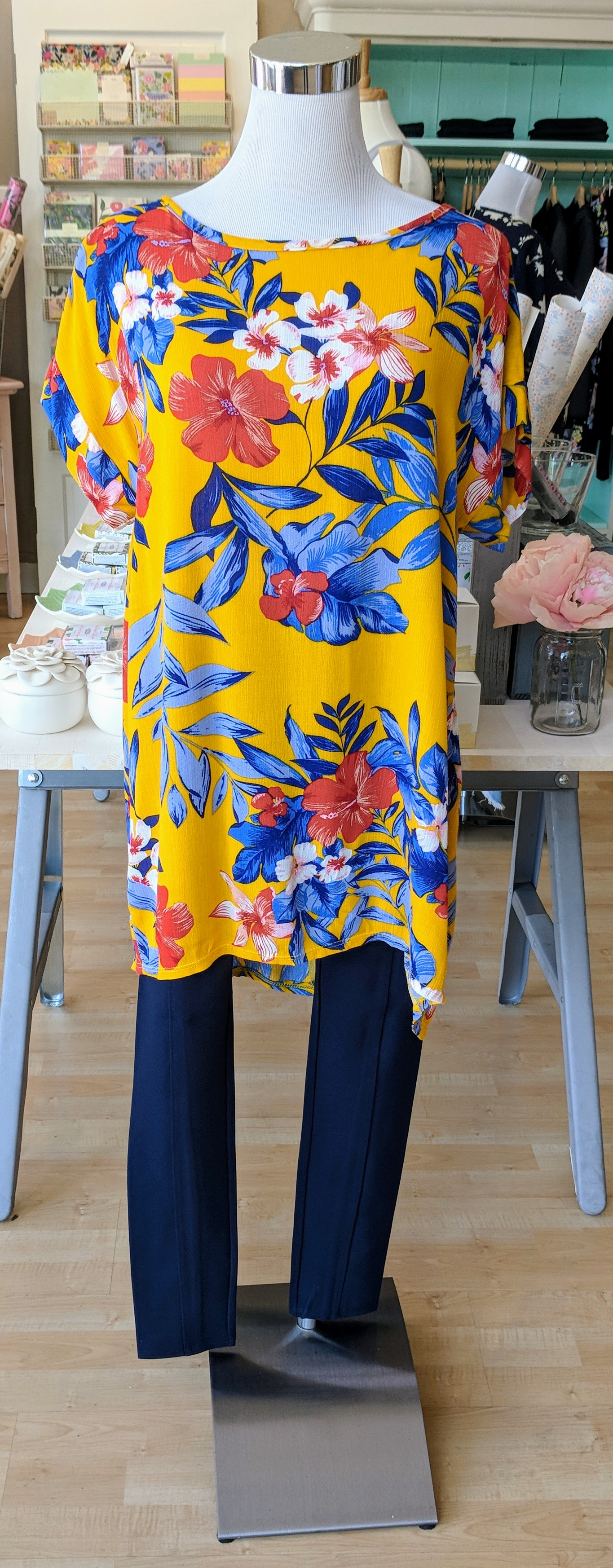 Mustard floral high low tunic top with criss-cross detail on back.