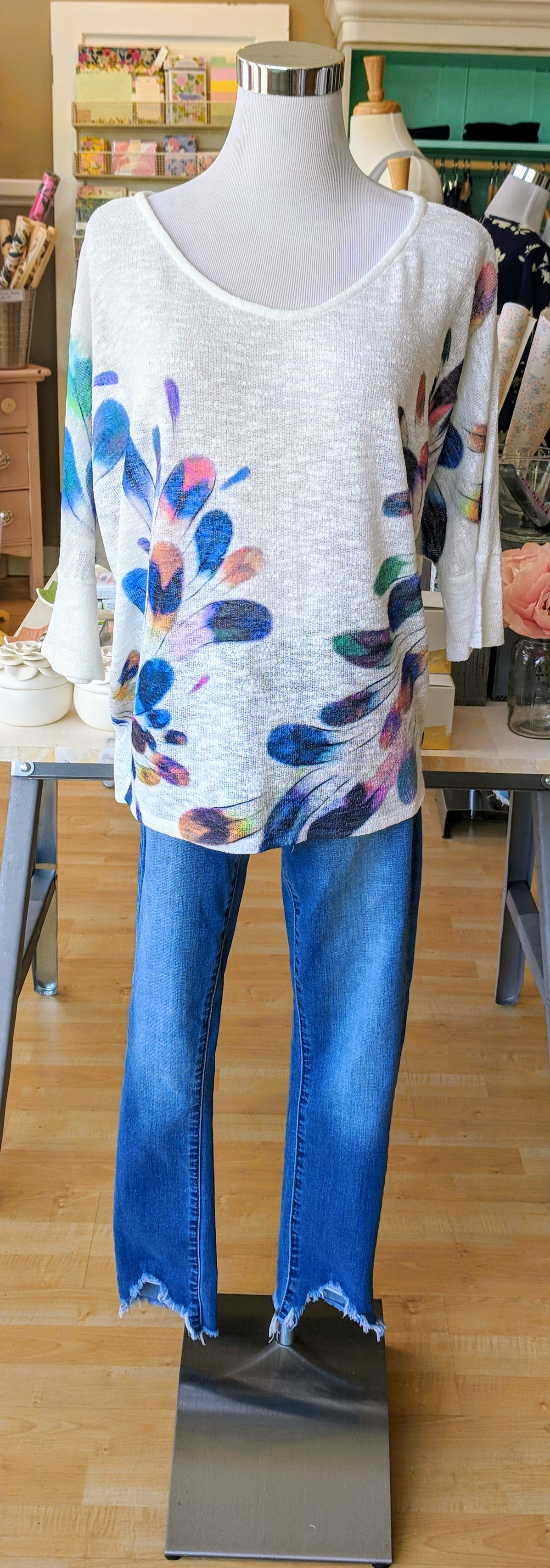 Ivory feather print top with scoop neckline.