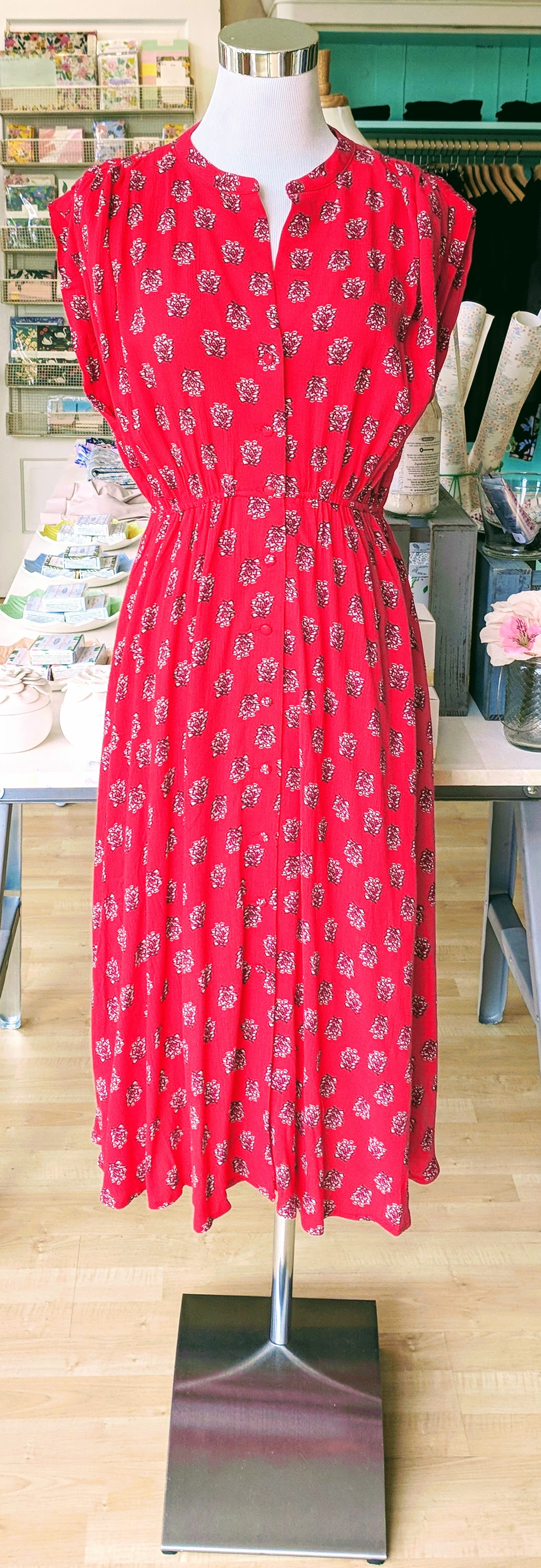 Coral sleeveless midi dress with button detail on front.