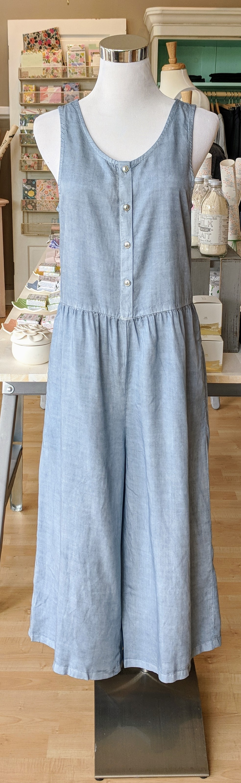 Faded denim jumpsuit with scoop neckline and button detail on front.