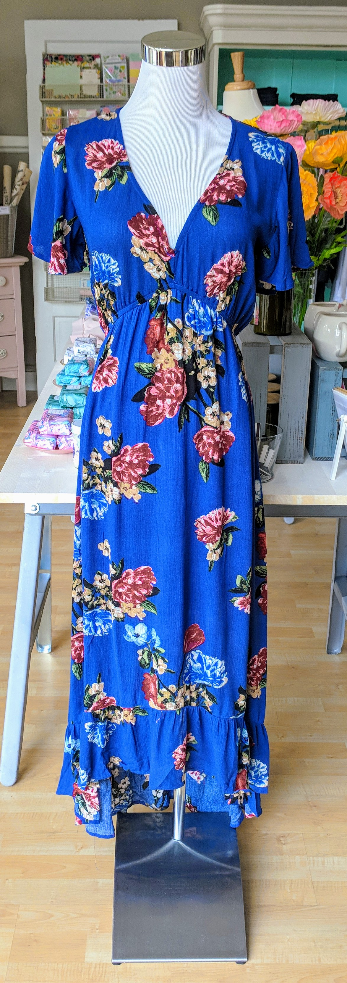 Blue maxi dress with flutter sleeve and lace inset on back .