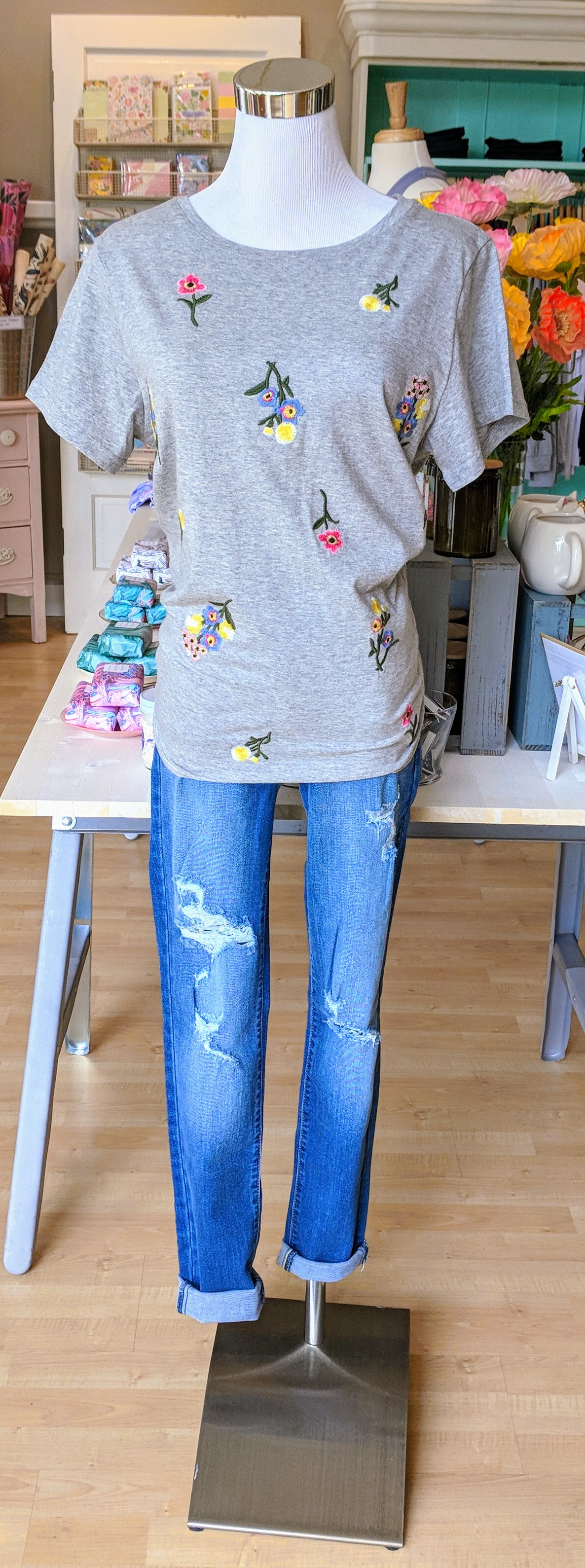 Grey top with embroidered floral pattern.