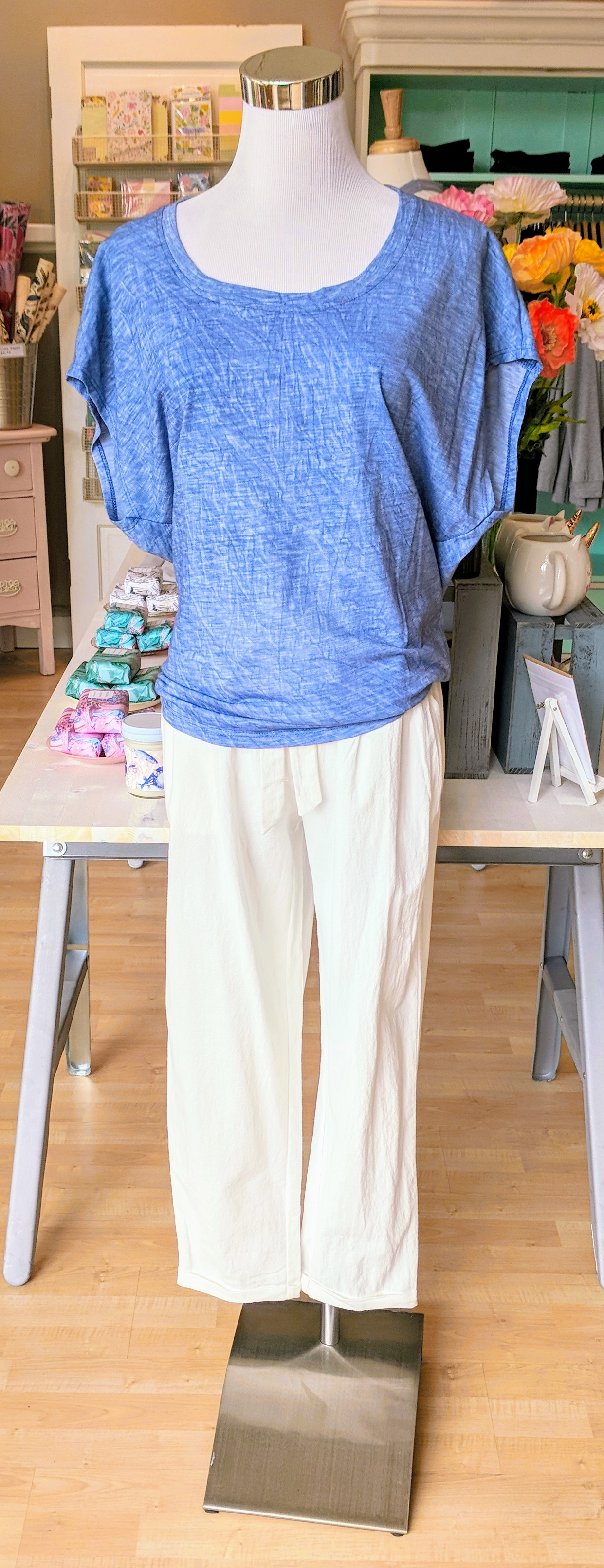 White linen pant with tie waist band. Blue knit top with dolman sleeve.