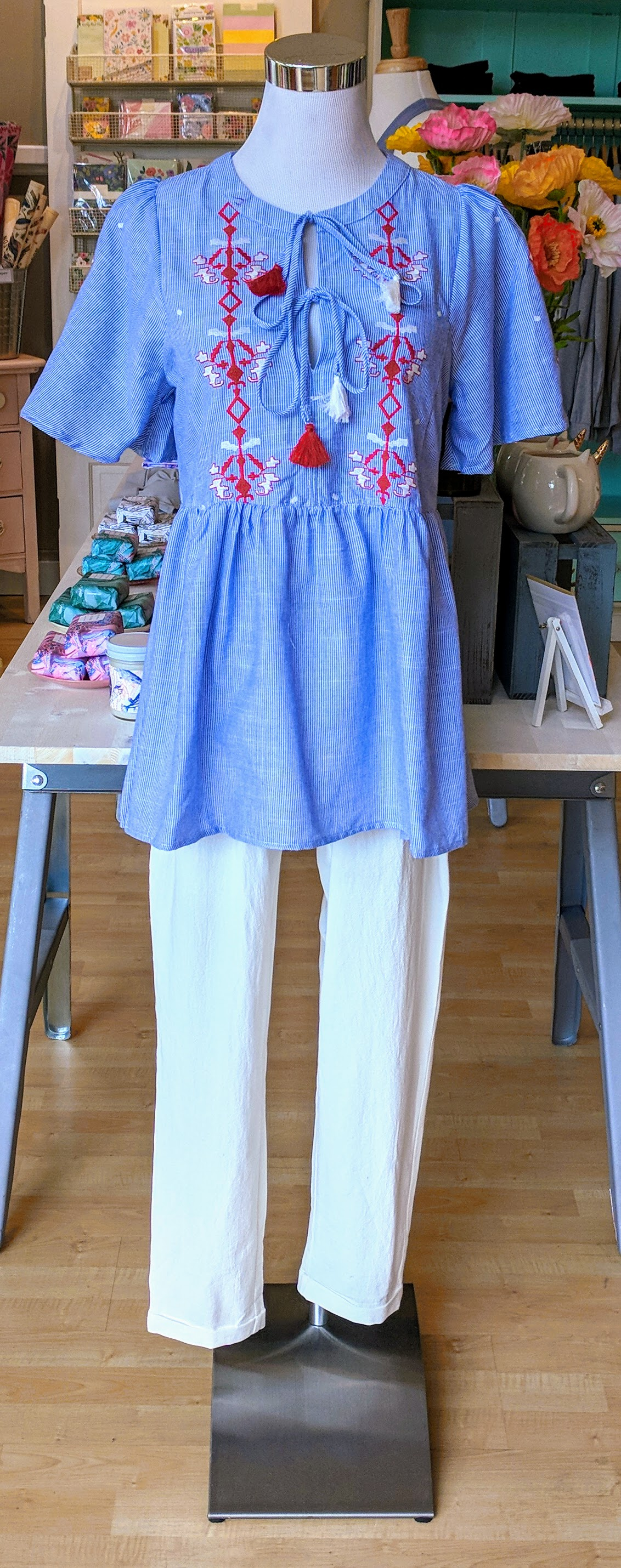Blue and red embroidered baby doll top with tie detail on front.