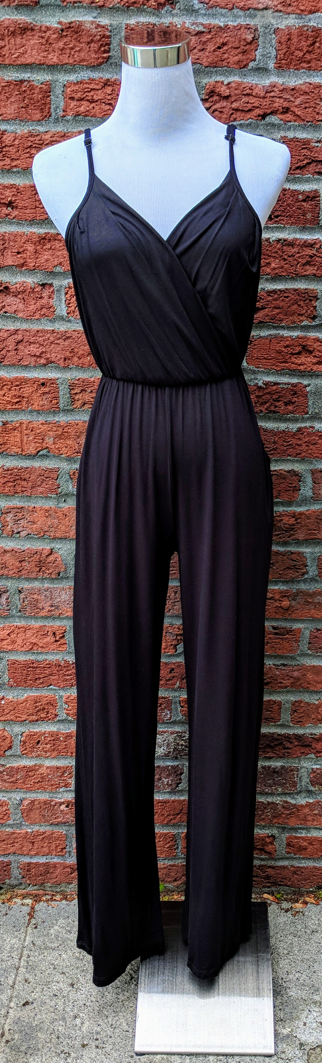 Black jumpsuit with cinched waist and adjustable straps.