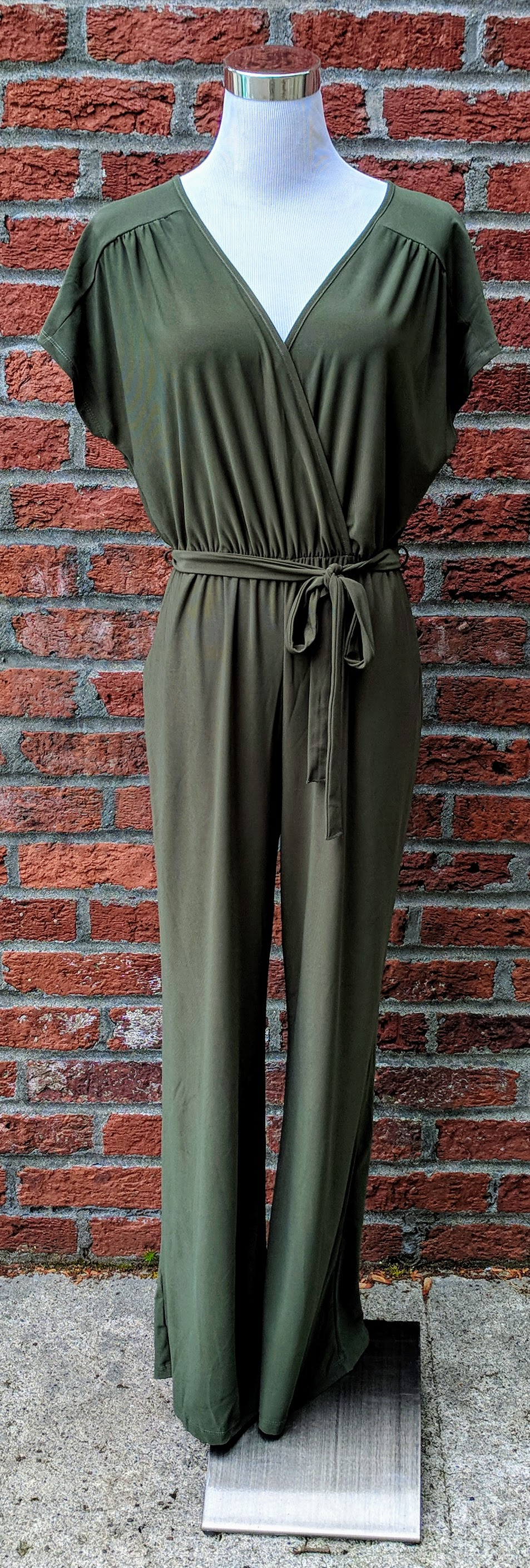 Olive jumpsuit with overlapped v-neckline and tie waist band.