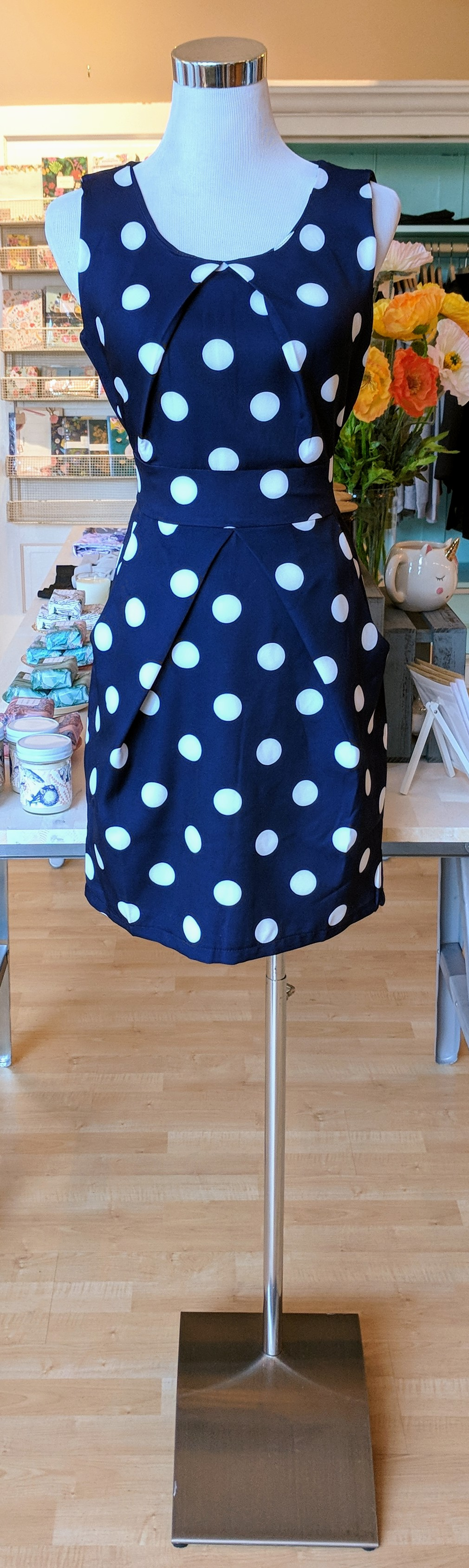 Navy polka dot sleeveless dress with pockets.