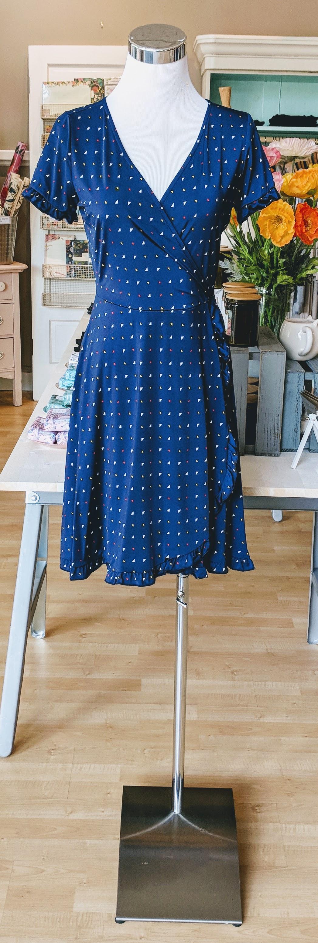 Navy triangle pattern wrap mini dress with ruffle hem.