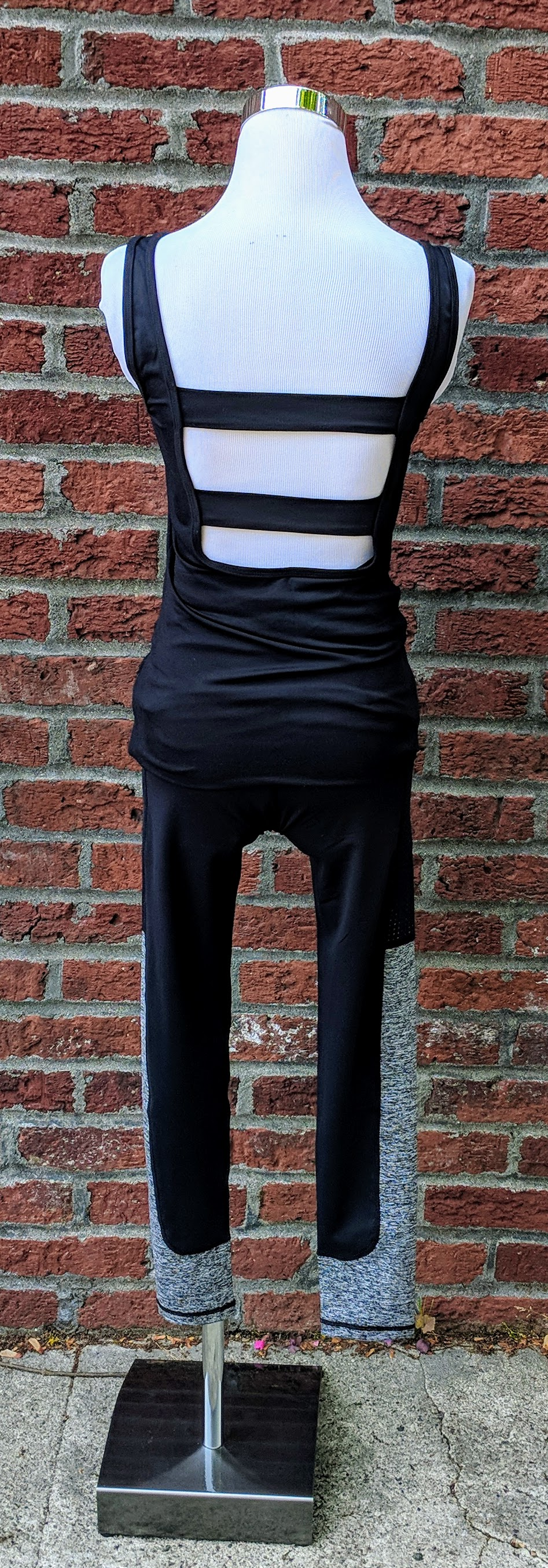 Black classic front tank with cut out panels on back featuring front zipper pocket.