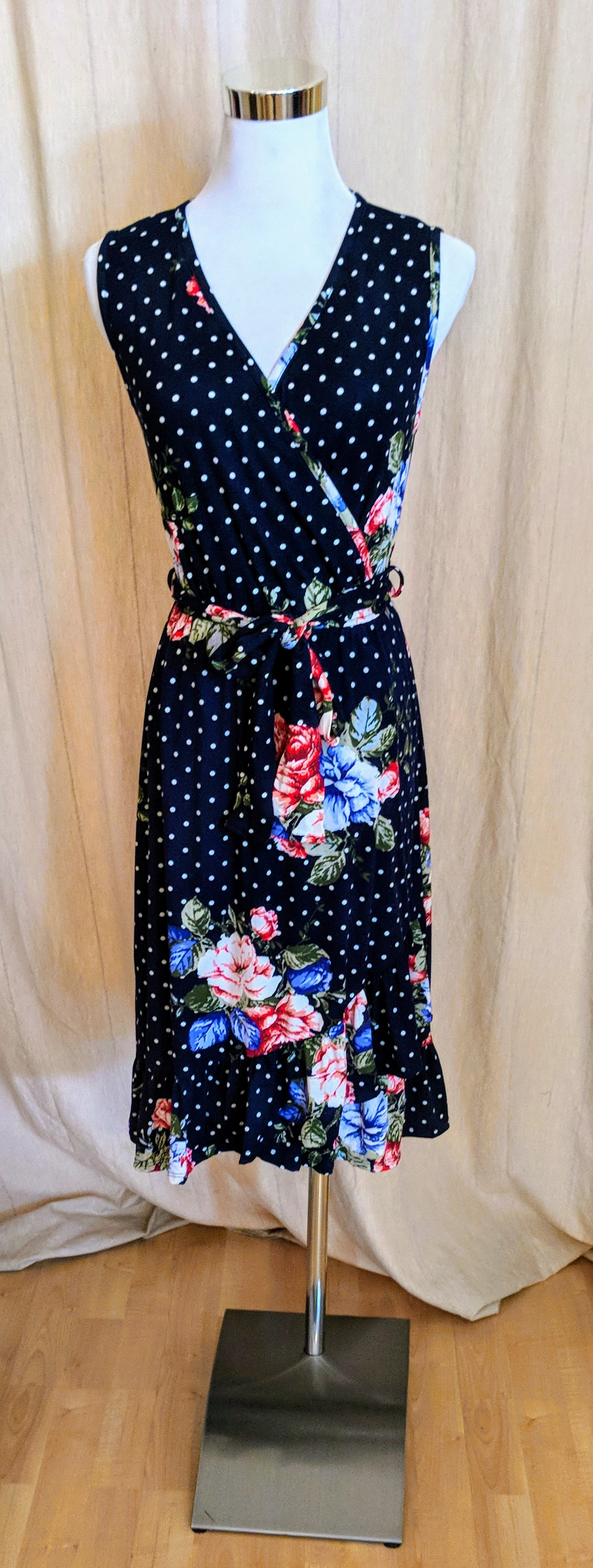 Navy sleeveless polka-dot and floral wrap dress with ruffled hem and tie on waist.