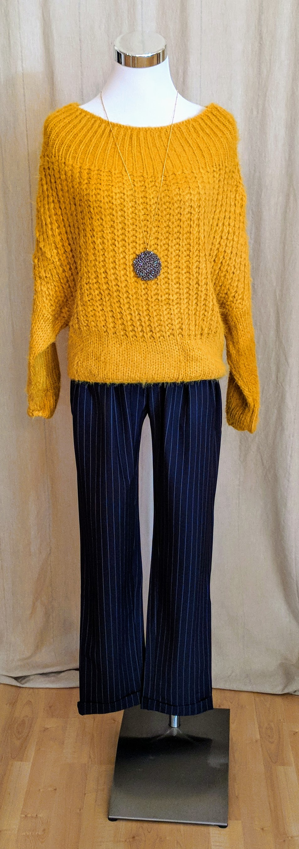 Mustard boat neck long sleeve knit sweater paired with navy high waist pleated trousers.