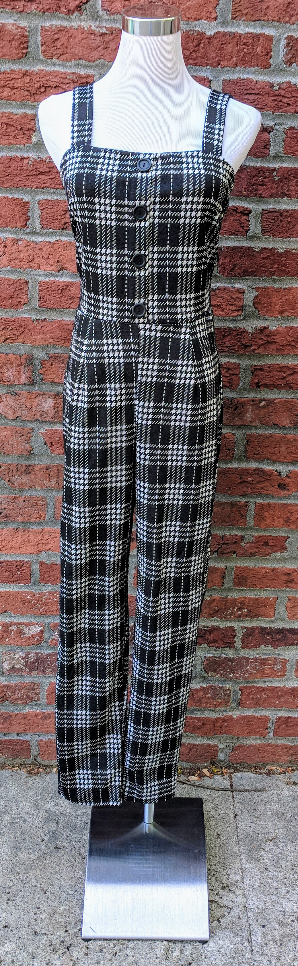 Black and white plaid jumpsuit with button detail on front.