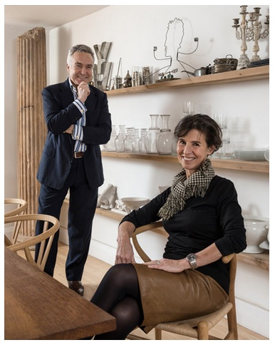 Stephen and Flo Bayley at their dining table and behind them the open shelves which are a feature around the house.