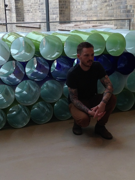"""This is Wintrebert posing by his cylinders. It's all about """"the balance of light and form, as well as the paradoxical strength and fragility of glass"""". And arm tats."""