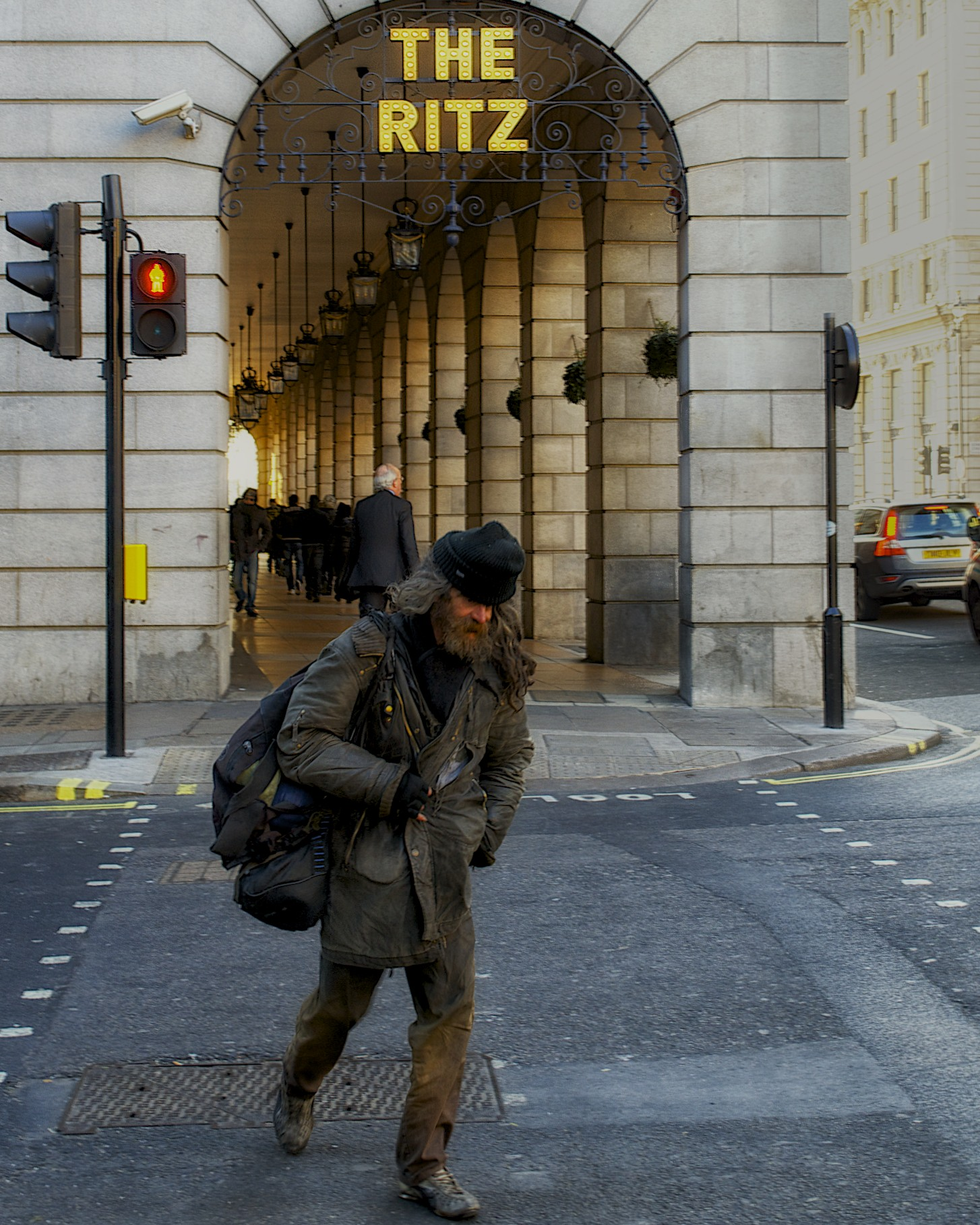 homeless guy walking past the ritz in london.jpg