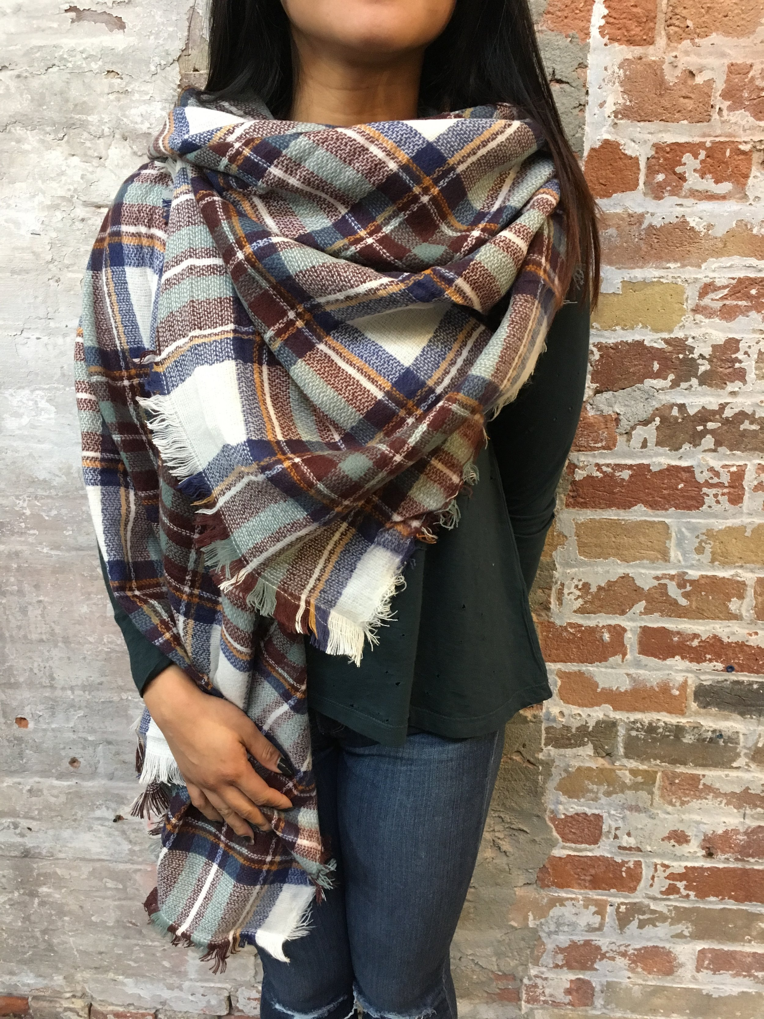 With a larger blanket scarf you have the option of wearing it as a cape! Fold the scarf into a large triangle and simply drape over you as desired, tucking in one corner at the neck to leave one flowing by your side.