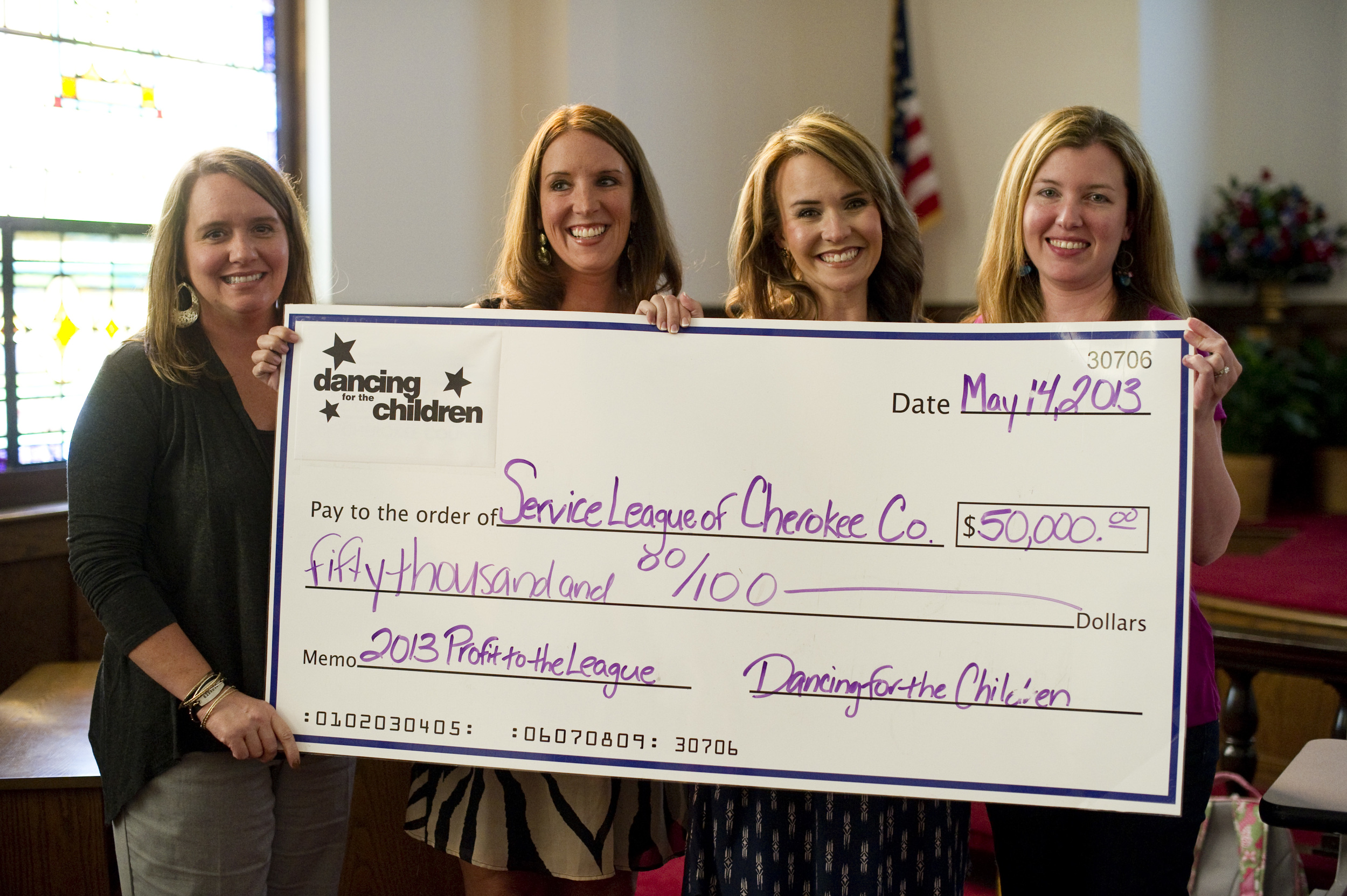 On behalf of the Annual Ball 2013 Committee, chairwomen (left to right) Holli Kimsey, Brittany Hayes, and April Turner present a check for $50,000 to Service League of Cherokee County President, Delane Stevens on Tuesday.