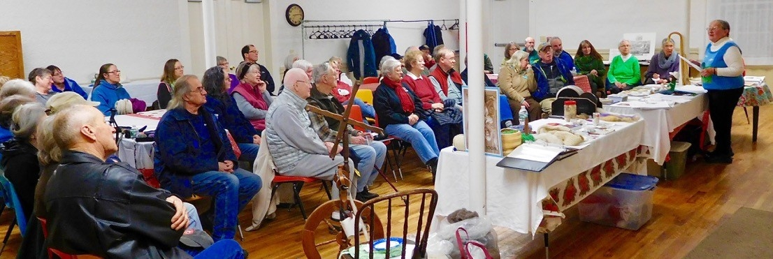 """Dori Hamilton presented a wonderful program, """"Sheep to Shawl"""" after the Society's Annual Meeting on January 18, 2017. There was a full house at the meeting space in the Shared Ministry's White Church in Lisbon. Dori's spinning wheel is pictured center right. Those present enjoyed a demonstration of the process of carding and spinning wool.. There was also a table of information about sheep and sheep farming, tools of the trade, photographs, and beautiful items made by Dori and her friends from her sheep's wool."""