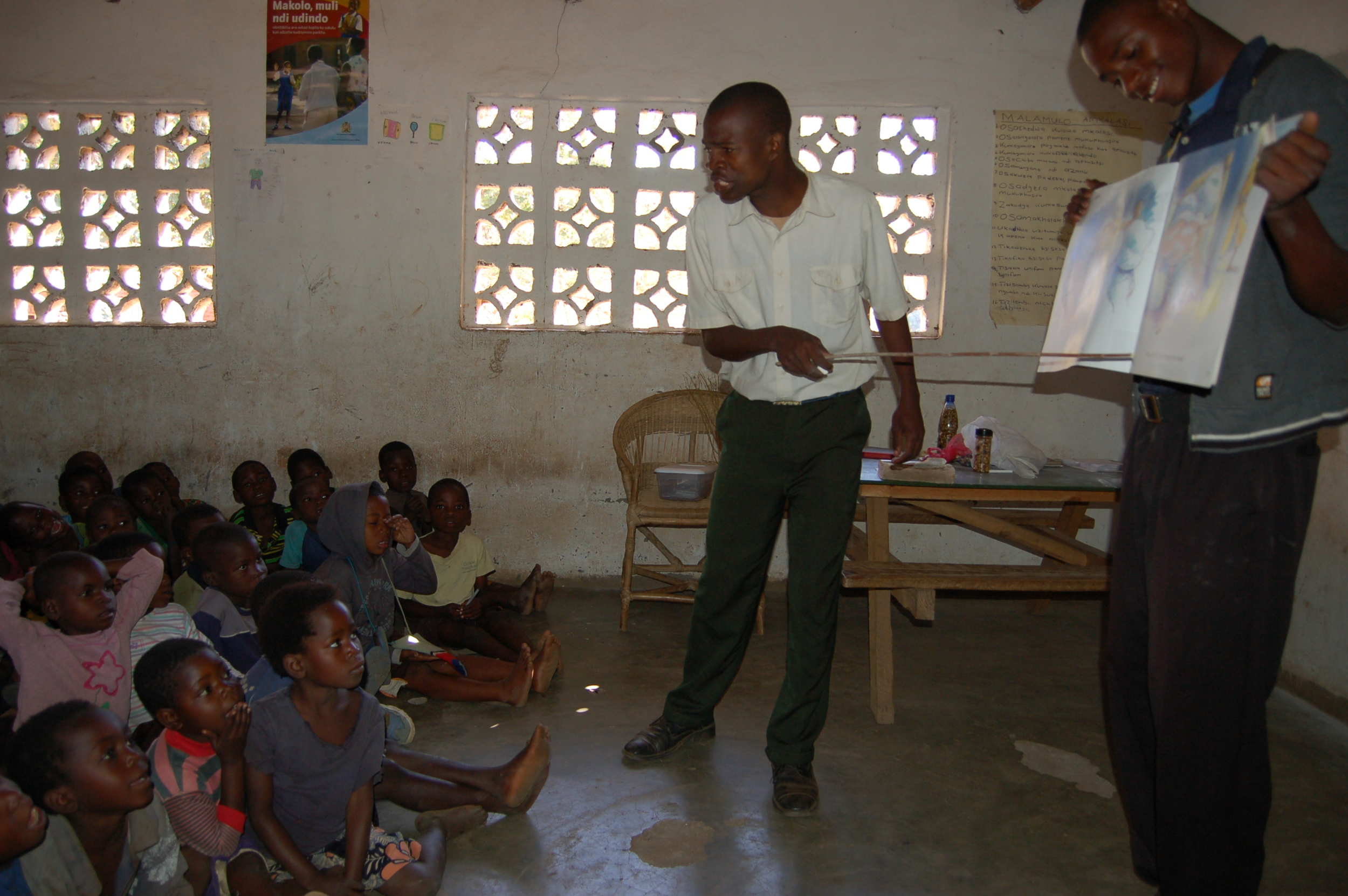 Simeon (holding book) teaching with another Grace Center staff member.