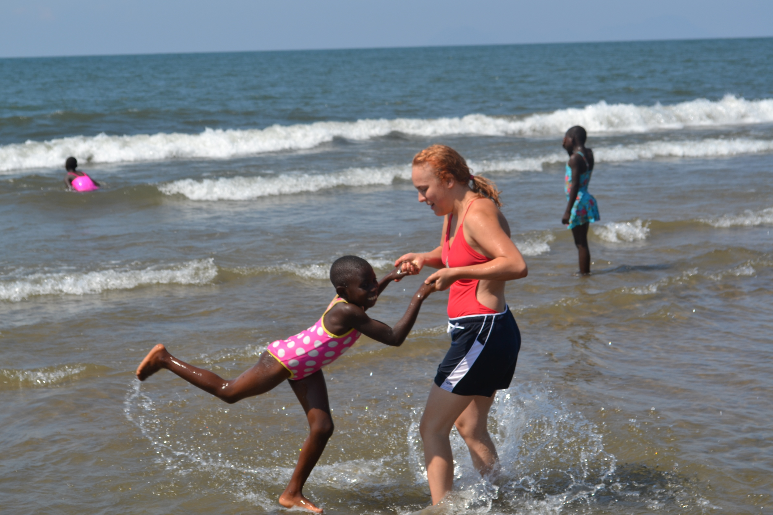 Amanda and Alinafe dancing in the waves.