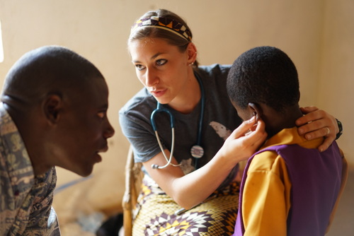 Karly Glibert working with Mr. Jairus in the clinic doing well-child exams.