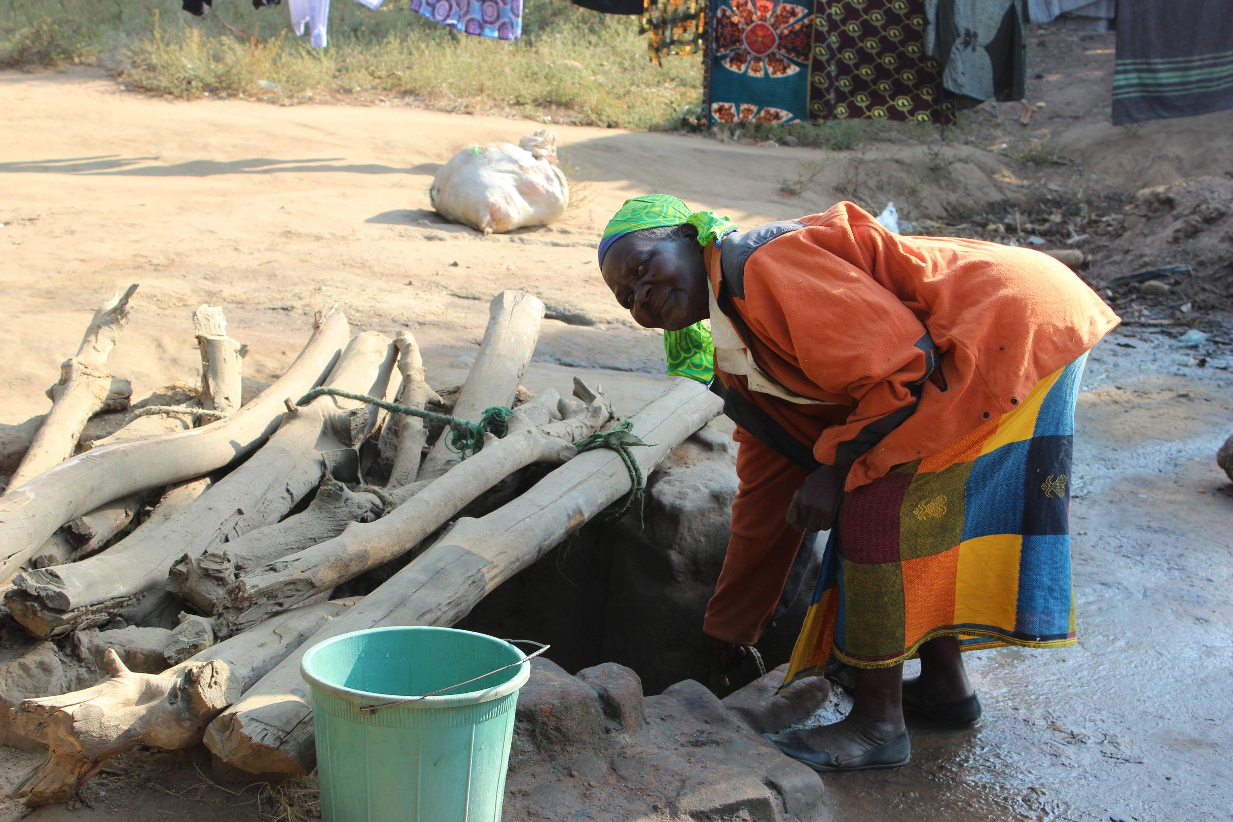 A Malawian grandmother drawing water from a hand dug well. Photo credit: Karen Roller 07/17
