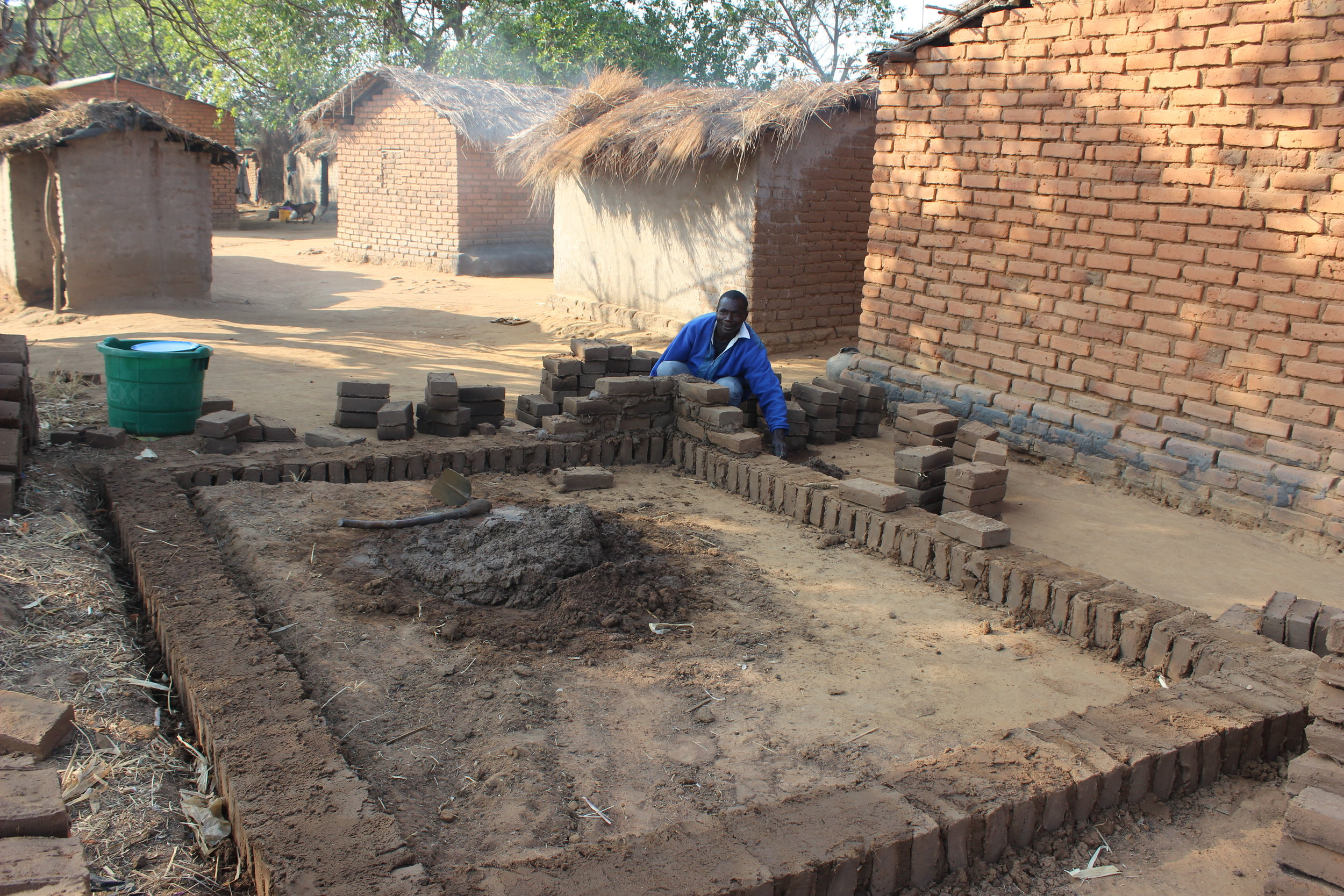 A Malawian father builds a new house for his family. Photo Credit: Karen Roller 07/17