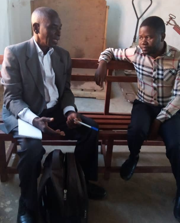 Pastor Andrew Ngwangwa and Dr. Levison Kawotcha deep in conversation regarding what type of toilets we'll build at Grace Clinic.
